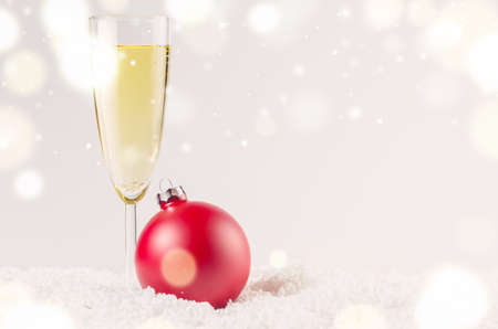 christmas baubles: red decorative christmas ball on snow against grey festive background with glass of sparkling wine