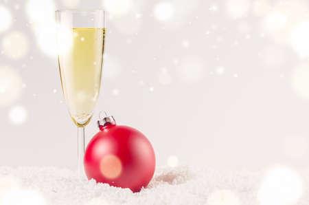 glas sekt: rot dekorative Weihnachtskugel auf Schnee gegen grauen festlichen Hintergrund mit einem Glas Sekt