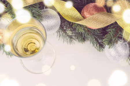 white christmas tree: glass of sparkling wine and decorative christmas balls with fir tree on white surface, view from above