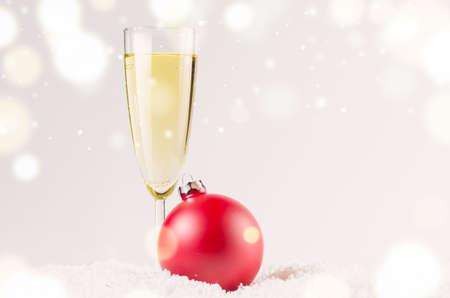 sektglas: rot dekorative Weihnachtskugel auf Schnee gegen grauen festlichen Hintergrund mit einem Glas Sekt