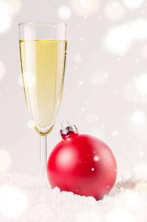 sparkling wine: red decorative christmas ball on snow against grey festive background with glass of sparkling wine