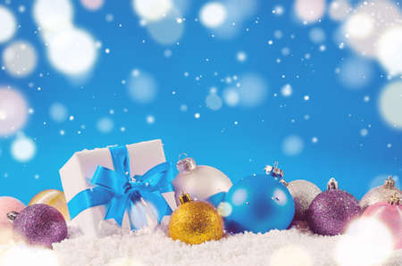 christmas gift box: white decorative christmas gift box with ribbon and balls on snow against blue festive background