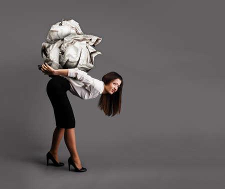 La mujer se inclina bajo el papel arrugado pesada