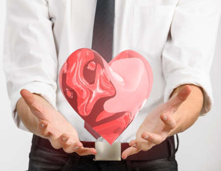 glass heart: Red glass heart is flying in hands of young businessman