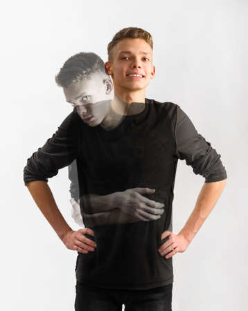 retribution: portrait of an insecure male caucasian teenager with two faces on gray background