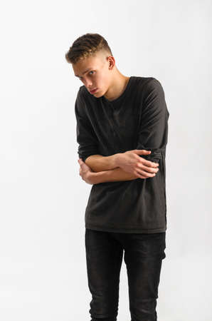 rolled up sleeves: portrait of a male caucasian teenager on gray background