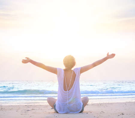 meditaion: young caucasian woman embracing the sea at sunrise beach