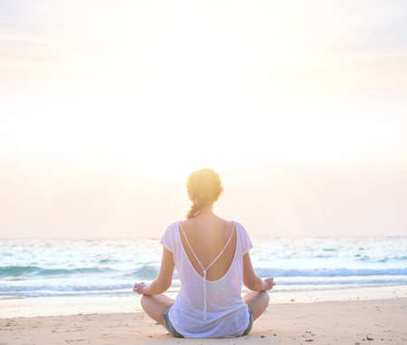 meditaion: young caucasian woman practicing yoga at sunrise beach