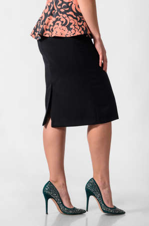 falda: vista lateral de una mujer con falda y tacones altos Foto de archivo