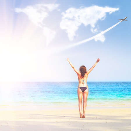 woman hands up: loving travelling. young woman on beach is trying to embrace continents shaped clouds Stock Photo