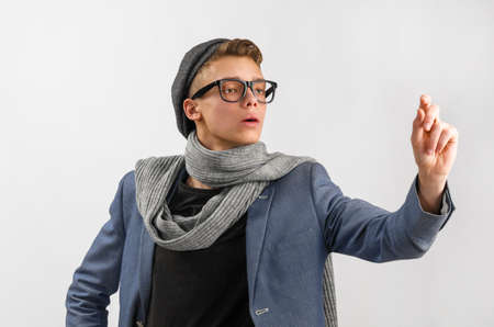 horizontal haircut: Portrait of a young artist wearing scarf and cap, against gray background