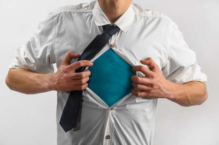 horizontal haircut: Young businessman showing suit of super hero with copy space under his shirt and tie on gray background