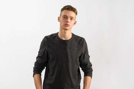 half length posed: portrait of a male caucasian teenager on gray background