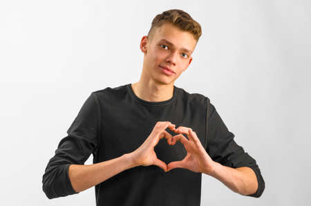 horizontal haircut: male caucasian teenager is showing his love on gray background Stock Photo