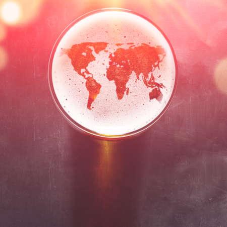 Silueta světové mapy na pěnu v pivním skle na černém stole, pohled shora