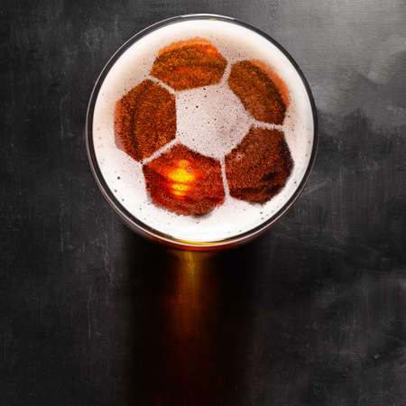 soccer or football ball symbol on foam of fresh lager beer glass on black table, view from above Stockfoto
