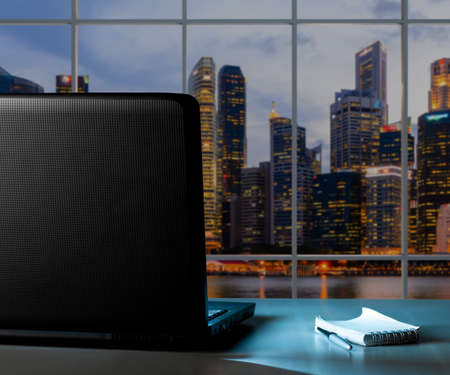 blurred background: modern laptop with blank screen on office desk at sunset Stock Photo
