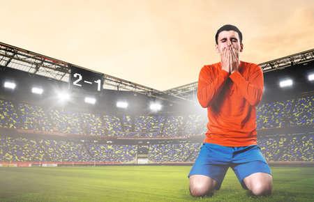 unglücklich Fußball- oder Fußballspieler knieten mit den Händen auf seinem Gesicht im Stadion nach unten Standard-Bild