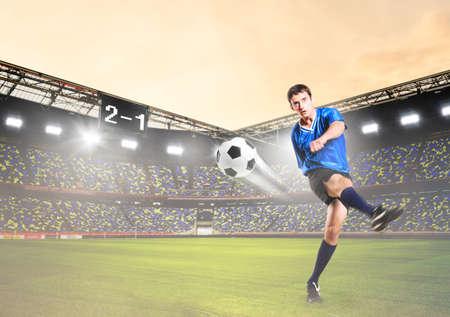 shot: soccer or football player is kicking ball on stadium Stock Photo