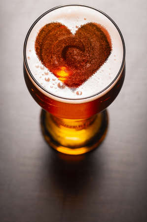 loving beer, heart symbol on foam in glass on black table, view from above Imagens - 57585252