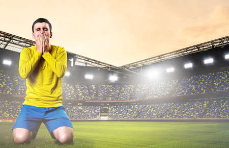 defeat: unhappy soccer or football player kneeled down with hands on his face at stadium