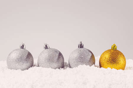 silver and golden decorative christmas balls on snow against grey background