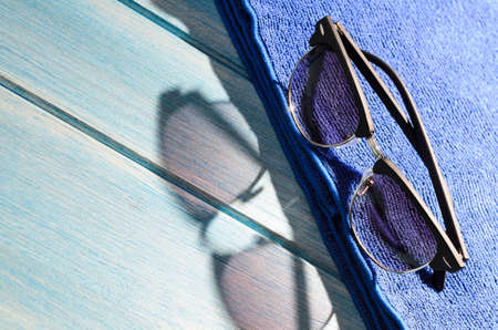 sun glasses: stylish sunglasses and towel on blue wooden table with sunlight