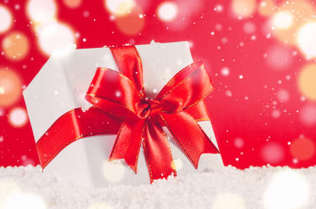 christmas gift box: white decorative christmas gift box with ribbon on snow against red festive background