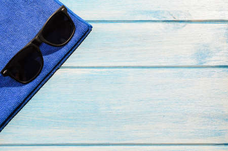 sun glasses: beach accessories. stylish sunglasses with towel on blue wooden table Stock Photo