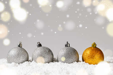 silver and golden decorative christmas balls on snow against grey festive background