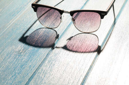sun glasses: stylish sunglasses on blue wooden table with sunlight