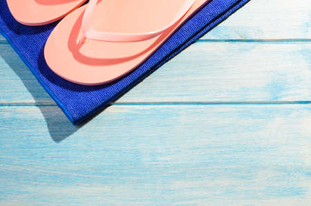 beach accessories. stylish towel and flip flops on blue wooden table