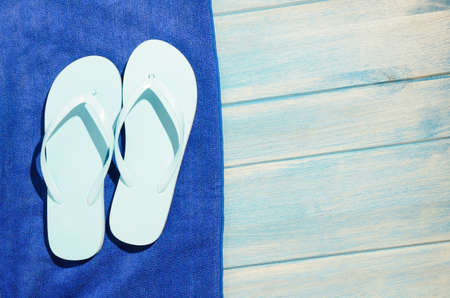 flip flops and towel on blue wooden table with sunlight