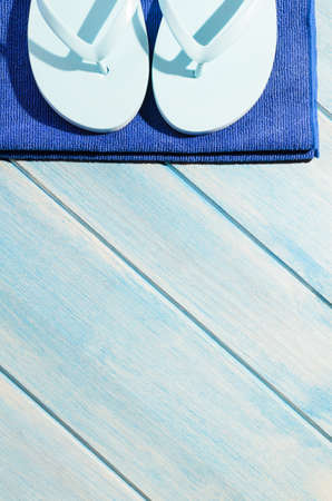 beach accessories. stylish sunglasses with towel and flip flops on blue wooden table Stock Photo