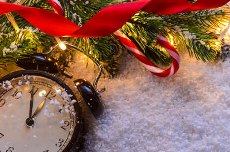 Christmas fir tree with lights and clock on snow in dark, view from above Stock Photo