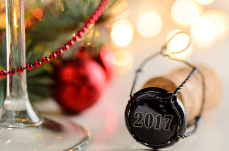 new year eve beads: sparkling wine or champagne cork on table with christmas or new year blurred background and decorated fir-tree Stock Photo