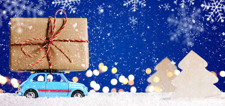 new car: Retro toy car delivering Christmas or New Year gifts on festive blue background
