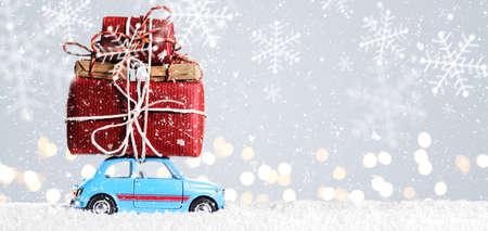 축제 회색 배경에 크리스마스 또는 새해 선물을 제공하는 파란색 복고풍 장난감 자동차