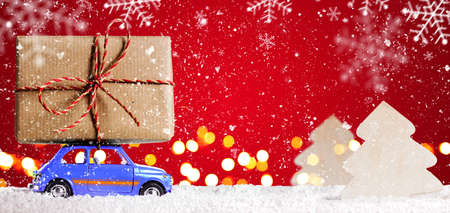 new car: Blue retro toy car delivering Christmas or New Year gifts on festive red background