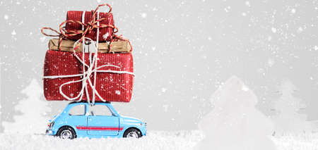 new car: Blue retro toy car delivering Christmas or New Year gifts on gray background Stock Photo