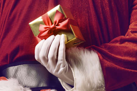 Santa Claus holding Christmas or New Year gift behind his back
