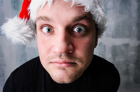young adult man: Funny Christmas celebration portrait of young adult happy man wearing Santa hat Stock Photo