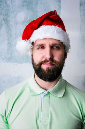 young adult man: Christmas celebration portrait of young adult bearded happy man wearing Santa hat