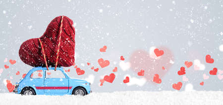 Blue retro toy car delivering heart for Valentines day on gray background