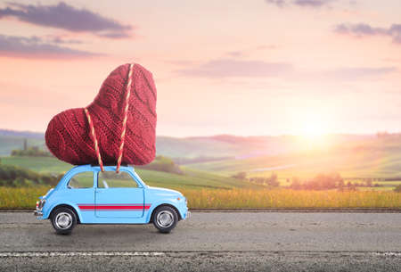 Blue retro toy car delivering heart for Valentine's day against blurred rural Tuscany sunset landscape Banque d'images