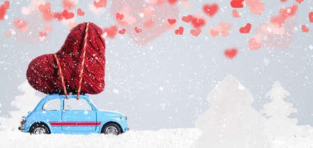 バレンタインの日に灰色の背景に心臓を提供する青いレトロなおもちゃの車