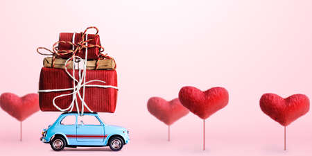 Blue retro toy car delivering gift box for Valentines day on pink background with heart trees