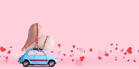 색종이와 분홍색 배경에 발렌타인 데이 공예 심장을 제공하는 파란색 복고풍 장난감 자동차