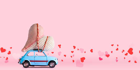 Blue retro toy car delivering craft heart for Valentines day on pink background with confetti