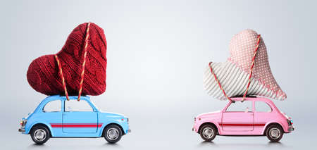 Couple of retro toy cars delivering craft hearts for Valentines day on gray background